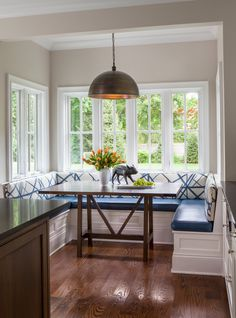 Eat-in kitchen nook, window seating, blue booth style seating, wood table, pendant lighting | Janet Mesic Mackie Photographer