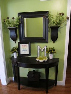 small entryway.  Black mirror and half table.  Flower sconces on either side.  I have a mirror and two candle sconces I'd like to paint and turn into vases...since I don't want to burn candles on the wall!!!