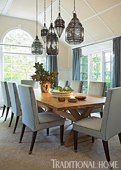 Hung at staggered heights, luminous lanterns from Morocco cast a dazzling glow on a rustic wooden table. - Photo: John Bessler / Design: Young Huh