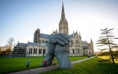 """A huge statue known as """"The Kiss"""" standing in front of Salisbury Cathedral in Wiltshire, England, had to be moved recently after passersby, texting while walking along, kept crashing into . Sophie Ryder, Salisbury Cathedral, Keep Walking, Land Art, Where To Go, Barcelona Cathedral, Places To Visit, Statue, World"""