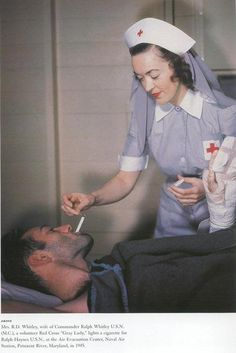 "A volunteer Red Cross ""Gray Lady"" lights a cigarette for U.S.N. sailor . 1945"