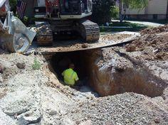 Obrero en un zanja con una excavadora encima