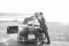 couple kissing on the back of a vintage car parked on the beach with vintage inspired clothing