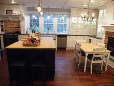 Pros & Cons of IKEA Cabinets - Gorgeous IKEA kitchen with fireplace. I love the farmhouse table and brick detail.