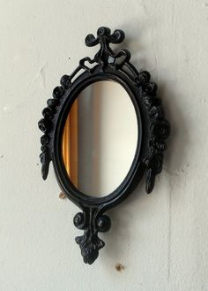 Oval wall mirror in revived vintage Italian brass frame with detailed rose borders and ribbon crest. I hand painted the ornate frame in jet black acrylic paint then sealed with a high quality gloss varnish. I also used a metal primer to ensure even paint color and a long lasting