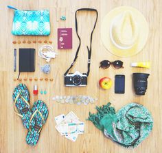 Wood background, printed blue makeup bag, brown sunglasses, green scarf, straw fedora, printed turquoise sandals, red nail polish, turquoise earrings, and camera