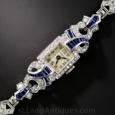 A dramatic and highly distinctive late Art Deco bracelet watch by Harvel Watch Co. - formerly of Rockefeller Center, New York. The artfully designed timepiece, rendered in platinum and sparkling white diamonds is strikingly accented with flowing ribbons of royal blue calibre sapphires. A singular stunner, circa 1930s-40s. 7 inches long.