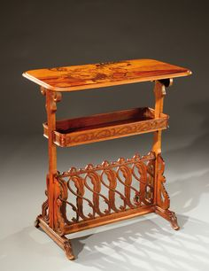 A walnut occasional table carved with floral motifs and coils and adorned with an exotic wood marquetry.Signe«E.Gallé» Circa 1900.