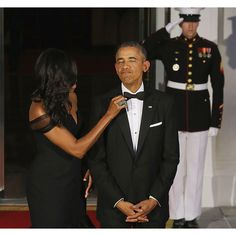 WASHINGTON, DC - SEPTEMBER 25:  U.S. First Lady Michelle Obama straightens U.S. President Barack Obama's tie while they wait on the North Portico for the arrival of Chinese President Xi Jinping and his wife Madame Peng Liyuan ahead of a state dinner at th