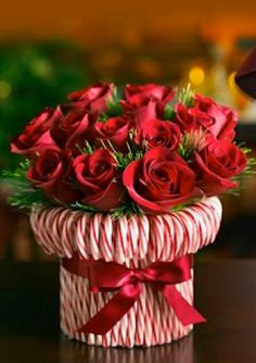 Candy Cane Vase - Stretch a rubber band around a cylindrical vase, then stick in candy canes until you can't see the vase. Tie a silky red ribbon to hide the rubber band. Fill with red and white roses or carnations. You could even use a recycled can to make a smaller version.