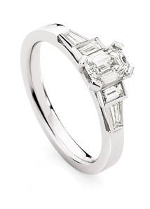 18ct White Gold Diamond Ring      Emerald cut centre diamond in 4 claw setting. On either side is a baguette diamond and tapered baguette diamond rub over set on 3 sides. The tapered baguette setting blends into the flat white gold band.      Would suit emerald cut diamond from 0.40ct.