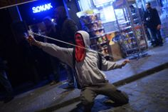 Bulent Kilic/AFP/Getty Images ON LINE: A protester used a slingshot during clashes with riot police in Istanbul, Saturday. Turkish riot police used tear gas grenades and water cannon to disperse more than 2,000 people demonstrating in Istanbul against new Internet curbs.