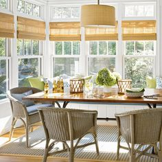 In the dining room, natural light streams through a bank of windows, and the color palette turns toward natural hues, with the bamboo blinds, bistro chairs, and large wood table.