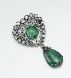 EMERALD AND DIAMOND BROOCH, LATE 19TH CENTURY The openwork heart-shaped surmount set with old-mine diamonds, supporting a pear-shaped emerald bead swing center, anchored by an emerald bead drop, both emeralds capped by rose-cut diamonds, mounted in silver and gold. With red leather and gold leaf embossed box.
