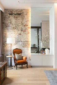 entrance hall. love this combo; antique and modern furniture. brick wall.