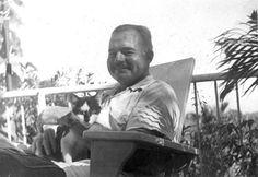 Ernest Hemingway sitting on a deck chair with cat, Boise, at his home, Finca Vigia, San Francisco de Paula, Cuba.