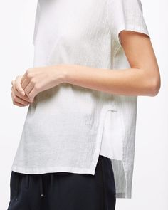 An update on the classic T-shirt, this piece is woven from 100% cotton with a silk trim for a contemporary, clean finish. A relaxed fit, features include a round neck and silk detail at the side seam. A timeless wardrobe staple.
