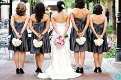 backsides of bridesmaids with flowers