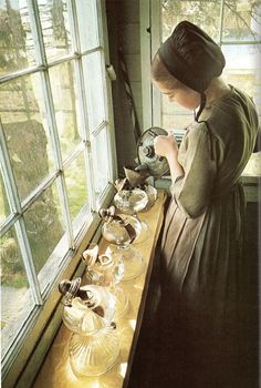 love this ... Amish girl preparing things on the window sill. Love it!   (My own great grandmother never used electricity but preferred oil lamps - we helped fill her lamps and also filled her corn cob storage for her wood burning stove - her heat and cooking)