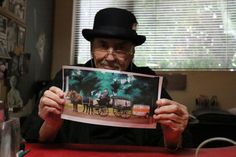 """Charles Bragg's studio in Southern California. The print he holds depicts a painting he had made for his friend, the comedian Jonathan Winters. It's Winters commandeering a hearse and proving wrong the saying """"You can't take it with you."""""""