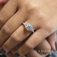 A subtle split shank adds interest to this classic engagement ring style. Shimmering pave diamonds abound, creating a halo around the center stone and adorning the band as well as the gallery. Round Halo Engagement Rings, Wedding Rings Simple, Classic Engagement Rings, Wedding Rings Vintage, Engagement Ring Styles, Wedding Jewelry, Halo Rings, Halo Diamond Rings, Elegant Wedding