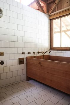 The wood construction extends to the Japanese-style family bathtub. Note the simple square tiles with dark grout applied to both the floor and the partial wall that divides the bathroom from the sink area while keeping it bright and airy. White Tiles Grey Grout, White Bathroom Tiles, Wood Bathroom, Bathroom Furniture, Small Bathroom, Master Bathroom, White Bathrooms, Wood Bathtub, Modern Bathtub