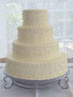 Stacked with Scroll & Pearl Embroidery - This cake is iced smooth with buttercream.  Scrolls and edible pearls accent the cake to replicate a wedding dress design.