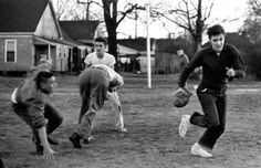 Elvis Presley playing touch football at the Dave Wells Community Center December 27, 1956. Several hundred people watched the singer pass, kick and run a touchdown.