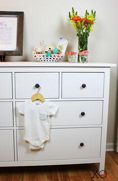 Cute Gender Neutral Baby Nursery With Dresser, Onesie, and Accessories.
