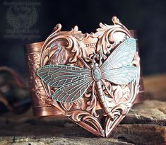 A bold and fantastic cuff with a rustic antique copper backdrop. A large, 2 wide etched cuff is done up in antiqued copper plated brass, American-made. We've added an ornate Art Nouveau heart stamping on the cuff, riveting it for extra durability, then topping it with a graceful curved dragonfly that has been accented in a tiffany green patina.      All metal is American-made brass with antiqued copper plating    Fastened with rivetsbolts for added durability    Cuff adjusts slig