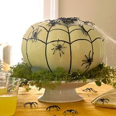 On the Menu  Serve a scary centerpiece for your next Halloween feast. Paint an artificial pumpkin with white acrylic paint. Use a black paint pen to draw on web: first (follow the veins of the pumpkin), then draw scalloped horizontal lines as shown. Adhere spider webbing to the top of the pumpkin and plastic spiders to the sides using crafts glue. Place the finished pumpkin on a cake pedestal and surround with greenery. Drape the spiderweb and scatter plastic spiders around for extra…