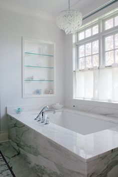 A sweet place for a chandelier - above a tub in a pretty marble bathroom.
