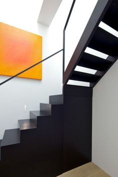 Black stairway, mix of open & solid stairs with black railing framing glass, design by  Found Assoc