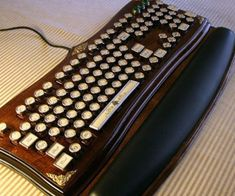 """Richard Nagy, aka """"Datamancer"""", specializes in handcrafted steampunk and retro-Victorian keyboards. His latest model, the Diviner, combines the two for an elegant assemblage of red mahogany woodwork and microchips. With matching wrist rest, no less. Ke"""