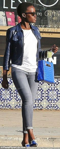 Standing out: Lupita topped her ensemble with a navy biker jacket as she clutched onto a leather handbag