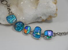 "This handmade artisan Dichroic Glass bracelet has amazing three-dimensional color in each original glass bead, set in 925-hallmarked sterling silver. Length: 6-7.5"" Adjustable toggle clasp. Widest cen"