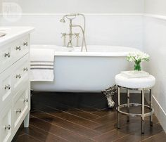 bathroom with freestanding tub and wood tile floor
