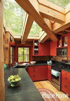 red cabinets, vintage rug, skylights, natural lighting
