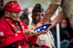 Honoring a Legend - U.S. Marine Corps Cpl. Chester Nez recieves an American flag from Pfc. Tiffany Boyd, at Code Talker Hall, Marine Corps Base Quantico, Va., April 4, 2014. The flag was flown over the Marine Corps War Memorial, on the first day of spring in honor of Cpl. Nez's attendace at the Platoon 382 Hall rededication. Cpl. Nez is the last of the original 29 Navajo Code Talkers of World War II.