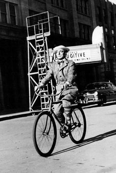 "Buster Keaton, on a coaster-brake bike winding his way down a street on the backlot, where John Ford's thriller, The Fugitive (1947), with Henry Fonda and Dolores Del Rio, is ""playing."" Keaton wears his getup for the 1949 MGM Judy Garland musical, In the Good Old Summertime. From Filmmaker IQ."