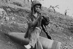 "Marine sits on an unexploded 16"" shell. Saipan 1944"