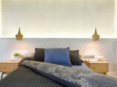 Frente del dormitorio en cemento y papel pintado con iluminación