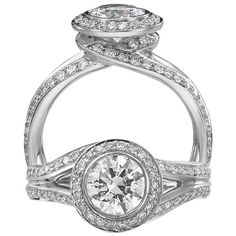Endless Love diamond engagement ring featuring a circular halo with a bezel set round cut centerstone that is surrounded by the finest micropavé set diamonds. The undergallery features a unique swirl design that continues down into a split shank, set with a single row of micropavé set diamonds.
