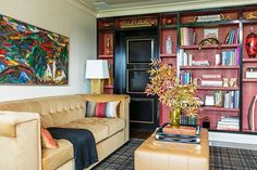 """The black-and-camel palette continues in the den, but with the addition of red in the form of a faux-shagreen wallpaper by <a href=""""http://www.ralphlaurenhome.com/"""">Ralph Lauren</a>. """"Not only does it provide another layer of color, but it's also a great backdrop for objects and books. Our client loves color, lacquer, reflection, shine, and shimmer,"""" says Lichten. Both the sofa and the ottoman are custom-made Lichten Craig designs by <a href=""""http://www.brusicrose.us/"""">Br..."""