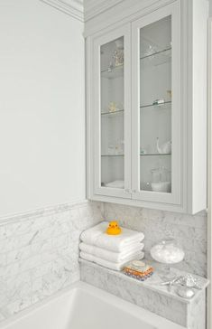 Beautiful bathroom features drop-in bathtub with white marble subway tile shower surround as well as glass-front cabinet painted gray over white marble tiled shelf filled with towels and rubber ducky.