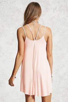 Style Deals - A jersey knit mini dress featuring a V-neck, double cami straps in a V-back, a raw-cut hem, and trapeze silhouette.