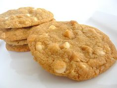 Great American Cookies-White Chocolate Macadamia Nut Cookie 1/2 cup butter, softened 1 cup dark brown sugar 1/2 cup coconut flakes, finely minced 1 egg 1 tablespoon milk 1 teaspoon vanilla extract 1 1/2 cups all-purpose flour 2 teaspoons baking soda 1/2 teaspoon baking powder 1/2 teaspoon salt 8 ounces solid white chocolate, cut into chunks 1 cup macadamia nuts, chopped