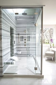 Amazing shower for two features walls clad in blue striped marble lined with blue striped marble floating his and her shower benches flanked by a seamless glass shower door.