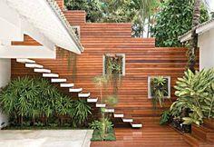 No terraço de 120 m² desta casa, o muro de 5 m de altura ganhou um tratamento especial: recebeu réguas de ipê. A escada não ficou para trás: os degraus de concreto, revestidos de lambris da mesma madeira, parecem flutuar. Sob ela, palmeiras ráfis com forração de grama-pêlo-de-urso e beijinhos compõem o canteiro de 2,50 x 0,90 m. As plantas maiores são podadas toda semana para evitar que atrapalhem o uso da escada. Projeto de Rita Santiago.
