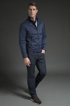 Polo marinho com vista listrada, sobreposta por tricô cinza em gola V e jaqueta de nylon marinho com recortes em matelassê, combinada com calça jeans raw. A modelagem da jaqueta e o tênis de camurça afirmam a referência esporte, tendência nessa temporada.